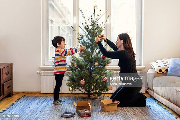 Boy and pregnant mother decorating Christmas tree