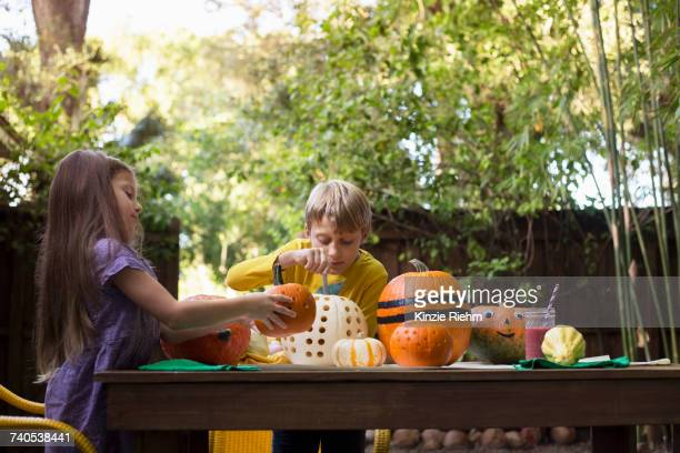Boy and sister carving pumpkins on garden table