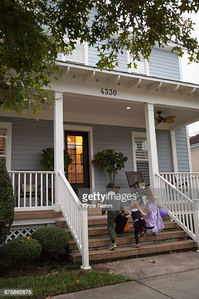 Boy and sisters trick or treating moving up porch stairway