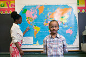 Boy and teacher at map in classroom
