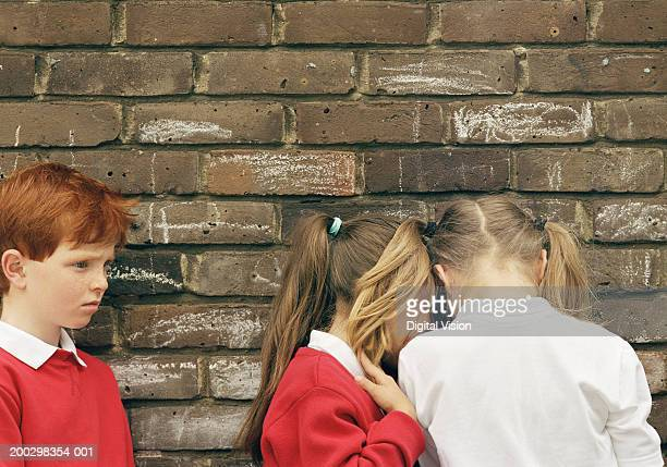 Boy (5-7) and two girls (6-8) standing by wall