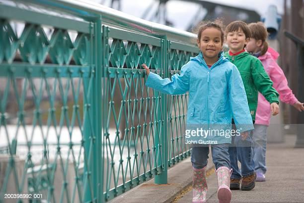 Boy and two girls (4-6) walking beside metal railing, smiling