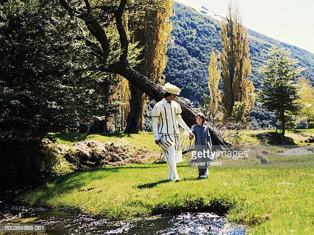 Boy (8-10) and young man in prince costume walking across field