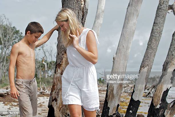 Boy and young woman exploring driftwood