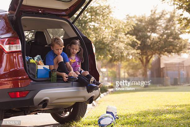 Boy and younger sister preparing for football practice whist sitting in car boot