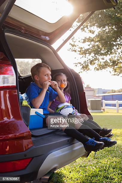 Boy and younger sister sitting in car boot eating oranges on football practice break