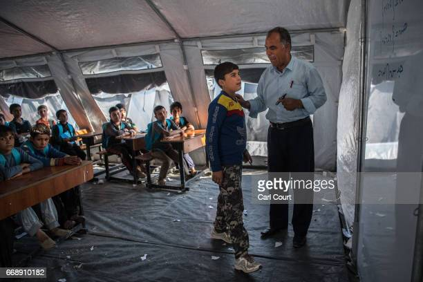 A boy answers a question posed by a teacher in class at a school in Khazir refugee camp on April 15 2017 near Mosul Iraq Khazir camp with a capacity...