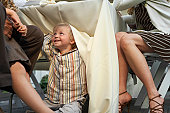 Boy (2-4 years) appearing from beneath table cloth of dining table on patio