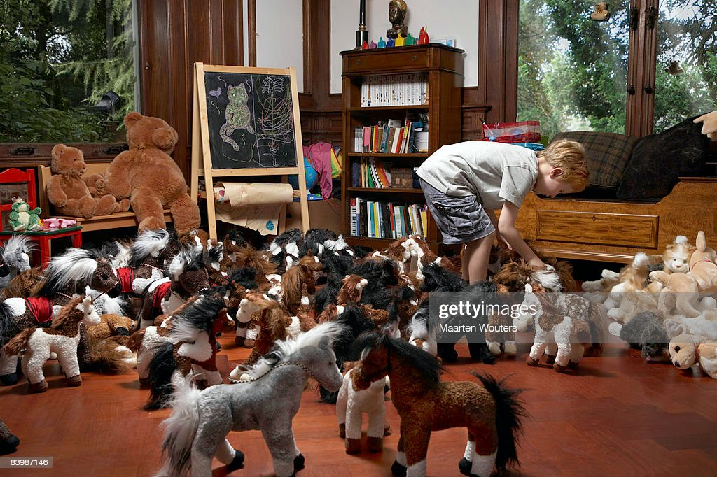 Boy arranging the toy horses in the play room : Stock Photo