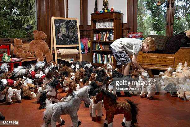 Boy arranging the toy horses in the play room