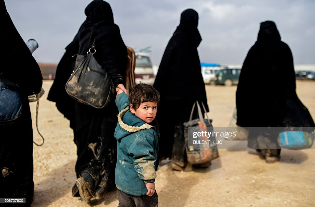 A boy arrives with women as Syrians fleeing the northern embattled city of Aleppo wait on February 6, 2016 in Bab Al-Salam, near the city of Azaz, northern Syria, near the Turkish border crossing. Thousands of Syrians were braving cold and rain at the Turkish border Saturday after fleeing a Russian-backed regime offensive on Aleppo that threatens a fresh humanitarian disaster in the country's second city. Around 40,000 civilians have fled their homes over the regime offensive, according to the Syrian Observatory for Human Rights monitor. / AFP / BULENT KILIC