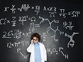 Boy as a professor with formulas behind him