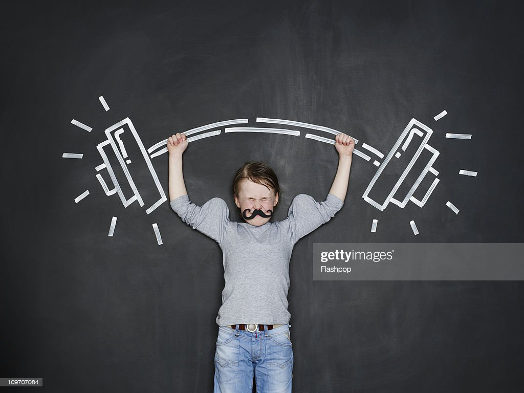 Boy as a strongman lifting heavy weight : Stock Photo
