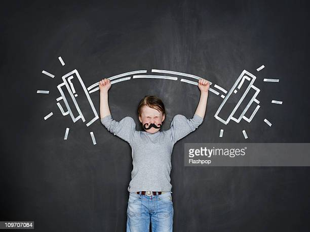 Boy as a strongman lifting heavy weight