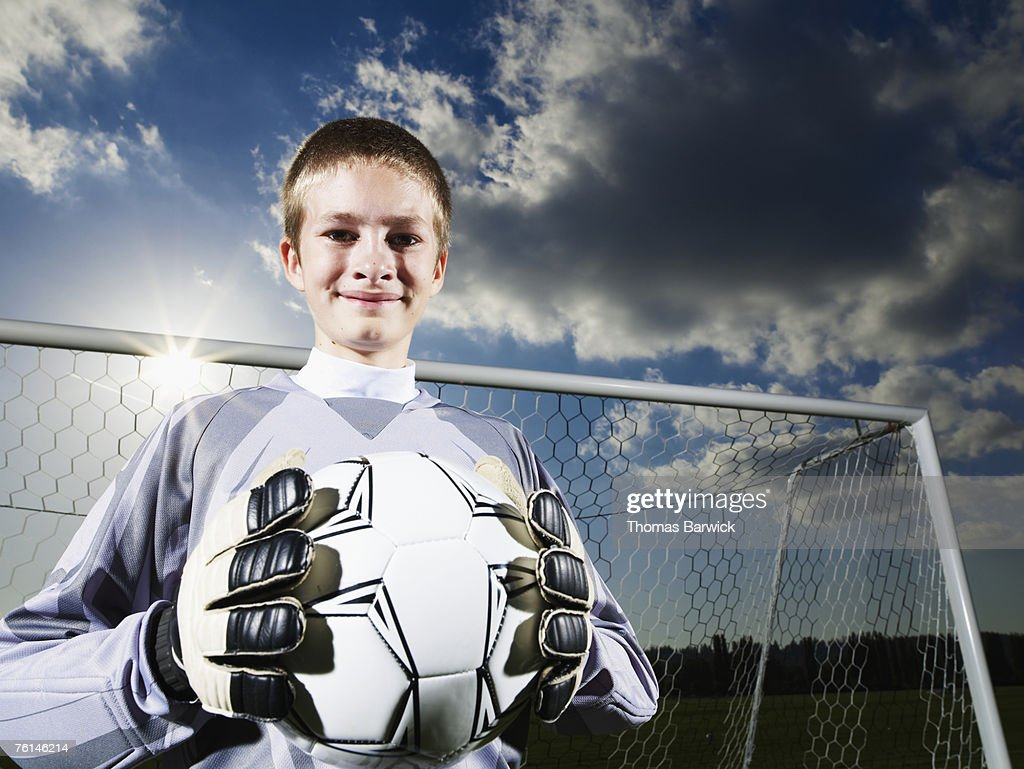 Boy (12-13) as goalkeeper, holding football in front of goal, portrait : Stock Photo