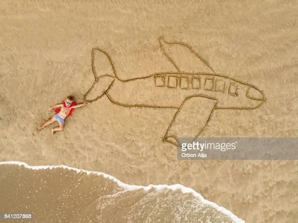 Junge als Superheld hält ein Flugzeug