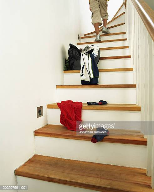 Boy (8-10) ascending stairs, sports kit on lower steps, low section