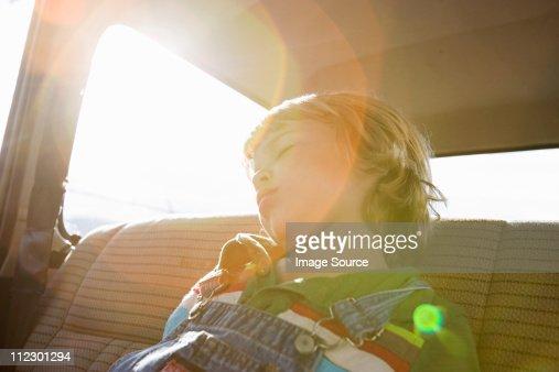 Boy asleep in back seat of car
