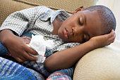 Boy asleep with tissue in hand