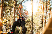 Young boy at the ropes course, enjoying adrenaline park adventure
