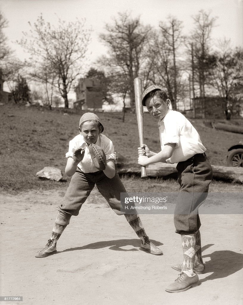Boy At Bat And Boy Catching, Both Wearing Knickers, Caps And Argyle Socks; One Is Wearing Sneakers, The Other Is Wearing Shoes Outside.. : Stock Photo