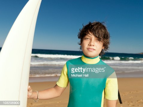 Boy at beach with surfboard : Stock Photo