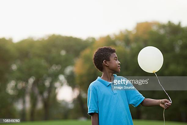 Boy at birthday party holding balloon