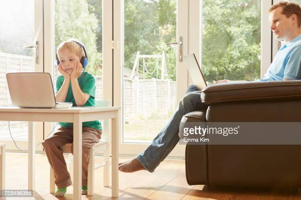 Boy at desk and father on sofa using laptops