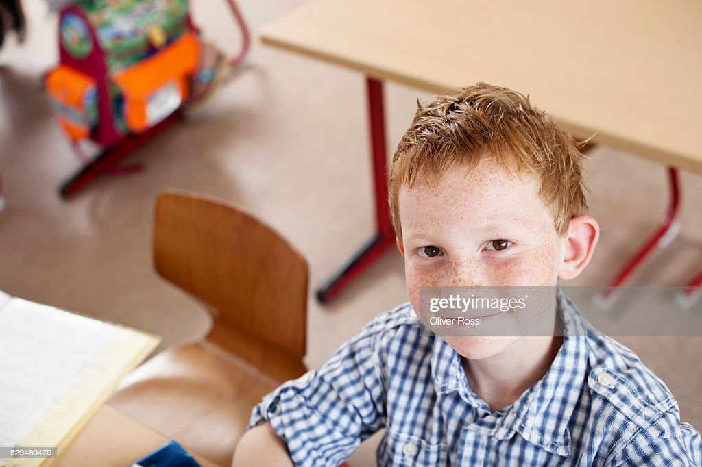 Boy at desk in classroom : Stock Photo