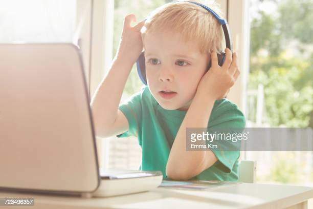 Boy at desk using laptop and listening to headphones
