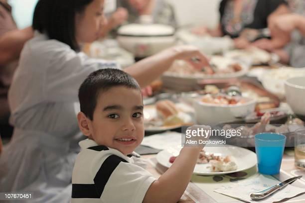 Boy at dinner table during Thanksgiving dinner