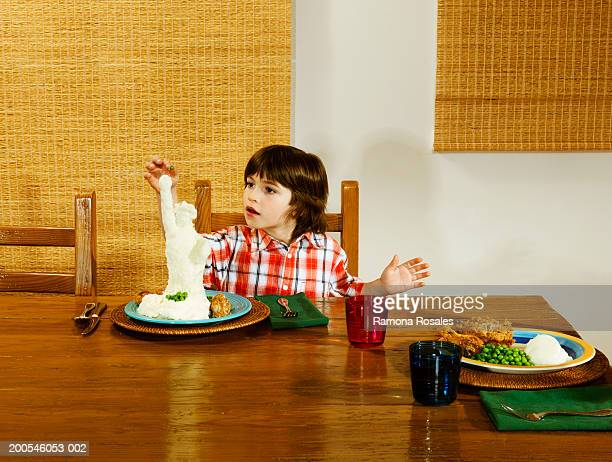 Boy (4-6) at dinner table  playing with food