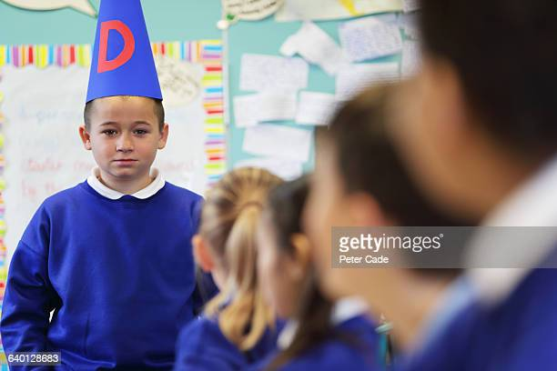 Boy at front of class wearing dunce cap