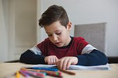 Boy at home making homework writing letters with colorful pens