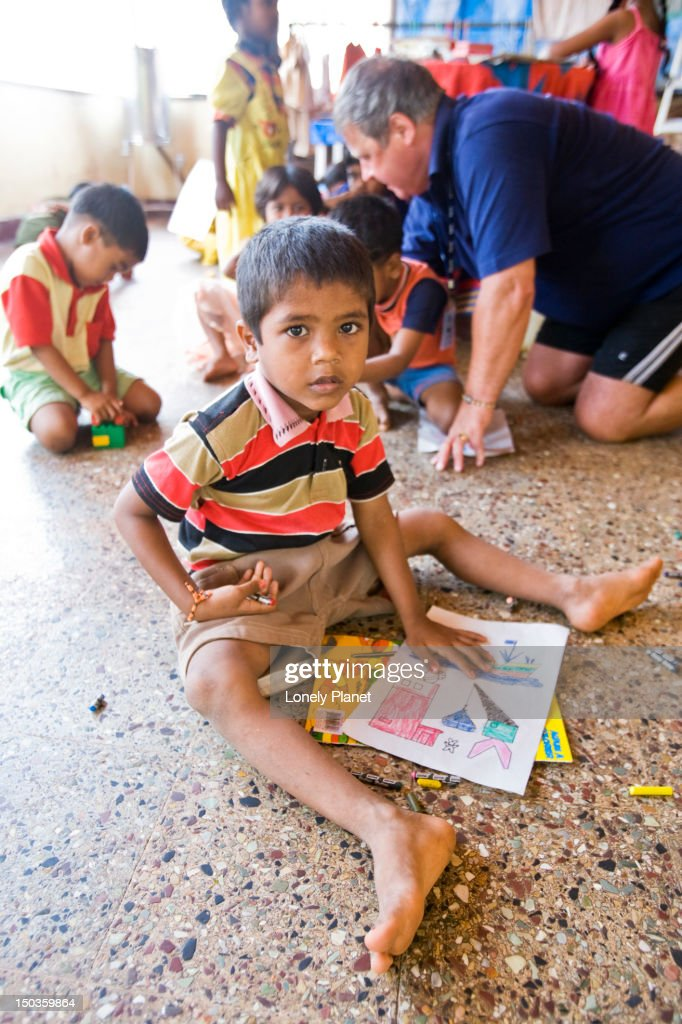 Boy at Little Acorns centre for disadvantaged children, with volunteeer at rear. : Stock Photo