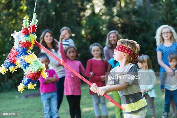 Jungen auf party erreichte Piñata mit stick