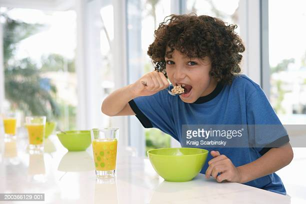 Boy (8-10) at table, eating cereal, portrait
