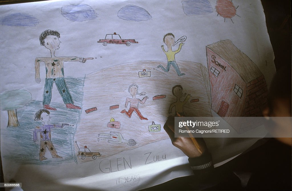 A boy at Xuma Primary School in Soweto, South Africa, draws a picture of white policemen shooting at black people outside a school, circa 1990. The class project is for pupils to depict the way in which they see white people.
