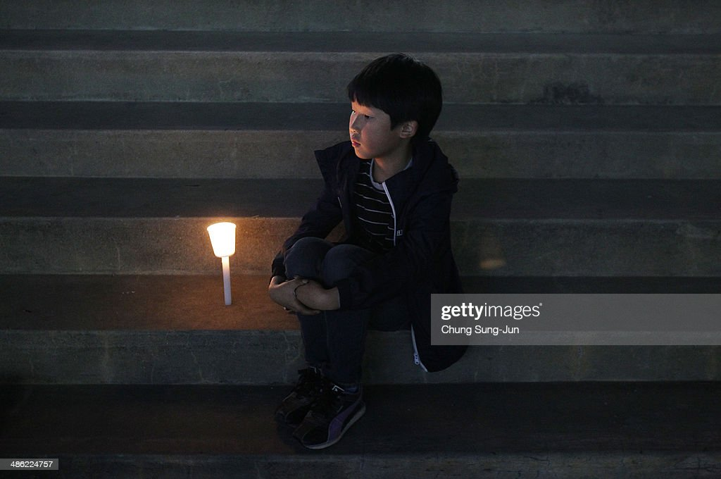 A boy attends a candlelit vigil for the safe return of missing passengers who were travelling aboard south Korean ferry the Sewol, which sank off the coast of Jindo Island, on April 23, 2014 in Ansan, South Korea. The confirmed death toll is reported to have risen to 150, with more than 150 people still missing.