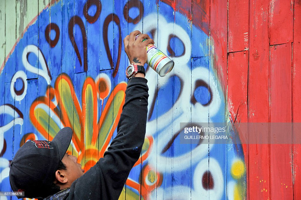 A boy attends a class of paint graffiti on April 26, 2016 in the municipality of Soacha, on the outskirts of Bogota, where an NGO promotes activities among some 300 at-risk children and teenagers. Through hip hop, graffiti art and other activities, the Proyecto de vida (Life Project) foundation - funded by Luxembourg NGO Children of Hope - is seeking to keep children in vulnerable situation away from drug addiction and crime. / AFP / GUILLERMO
