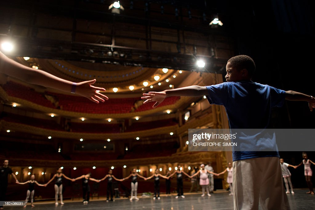 A boy attends a classic dance class given by teachers from the Royal Opera House to children from Brazilian dance schools and from shantytowns, at the Municipal Theater in Rio de Janeiro, on February 23, 2013. The Royal Opera House of London landed in Rio this week with educational programs and events that include dance lessons for children living in the city's shantytowns. AFP PHOTO/Christophe Simon