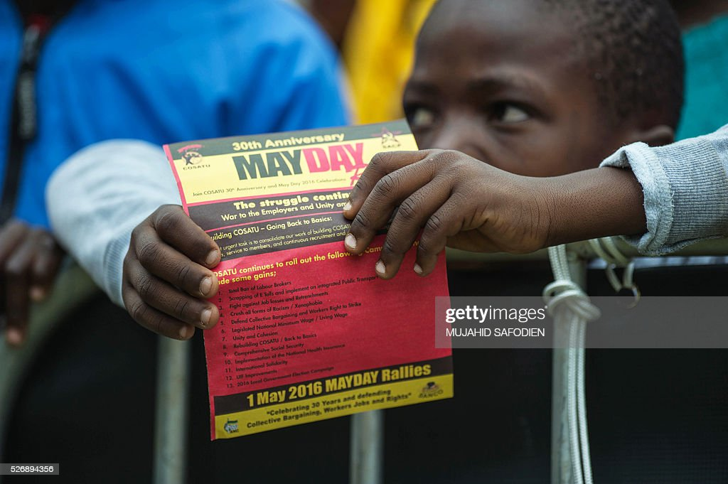 A boy attends the congress of South African Trade Unions (COSATU) as part of the May Day rally at Mamelodi's Moreleta park on May 1, 2016 in Pretoria. Secretary General Sdumo Dlamini, South African Communist Party leader Blade Nzimande and South African President Jacob Zuma took part in the rally. / AFP / MUJAHID