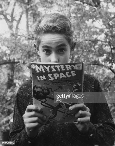 A boy avidly reading the back cover of a comic book entitled 'Mystery In Space' circa 1960