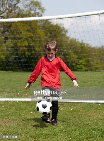 Boy balancing a football : Stock Photo