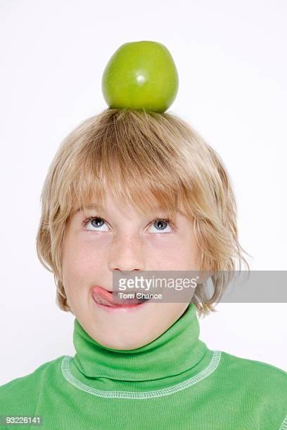 Boy (10-11) balancing apple on head, close-up