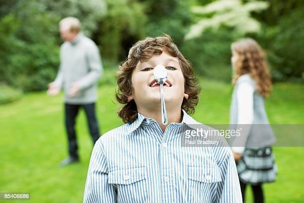 Garçon équilibrant cuillère sur le nez