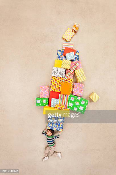 Boy balancing stack of presents