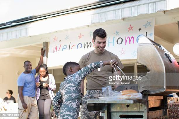 Boy barbecuing burgers with male soldier at homecoming party