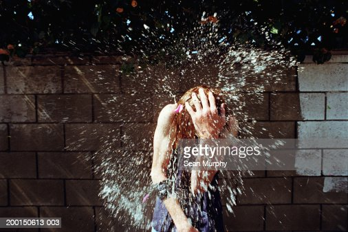 Boy (13-15) being hit with water balloons