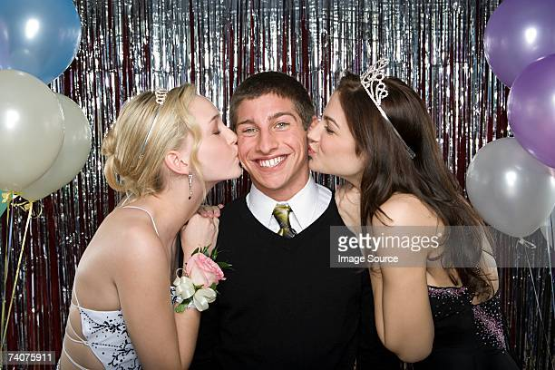 Boy being kissed by two girls